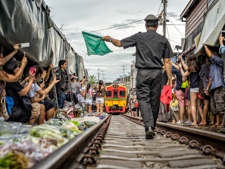 MAEKLONG, THAILAND - MAY 14, 2017: Maeklong railway market (Talad Rom Hub) with many tourists. Train passing through local market is popular tourist attraction close to Bangkok in Thailand. Editorial