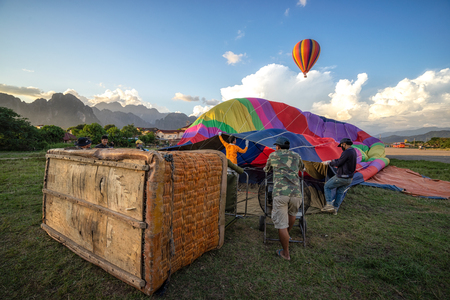 VANG VIENG, LAOS - NOVEMBER 15, 2016: Hot air balloon. Crew is securing parachute vent. A burner directing a flame into the envelope. Hot-air ballooning is popular tourist activity. Sajtókép