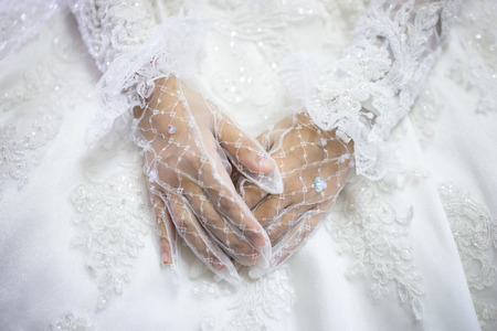 Woman in white wedding dress, bride hands in white bride gloves. Traditional Islamic hijab wedding dresses. Muslim brides who spent their wedding day wearing the most incredible veils called hijabs.