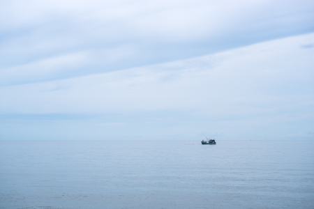 Fishing boat in the calm sea ocean and blue clear sky background. Gently blue and aquamarine colors.
