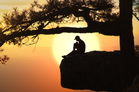 Beautiful views of the sunset with reflect silhouette of the pine tree and male tourist.