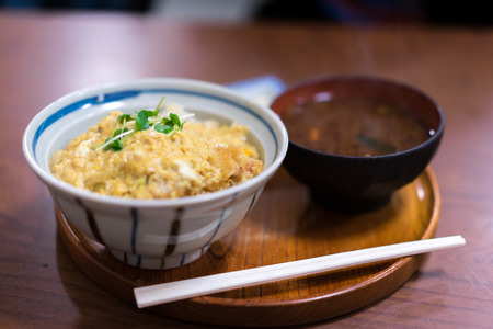 Katsudon served in a large Japanese rice bowl with a pair of chopsticks. Banco de Imagens