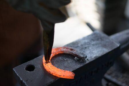 Professional blacksmith at Lampang, Thailand making a horseshoe.