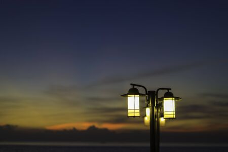 Street lamps at night. A brightly lit street lamps at sunset. Banco de Imagens