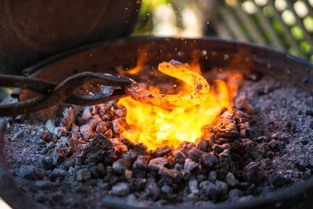Blacksmith making a horseshoe in small forge.