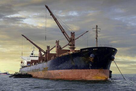 A cargo ship or freighter ship on sea with cloudy sky. International trade. Banco de Imagens