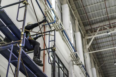 Worker sitting on the scaffolding at the construction site. Banco de Imagens