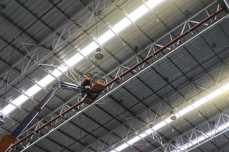 Worker standing on an articulating boom lifts in the factory. Banco de Imagens