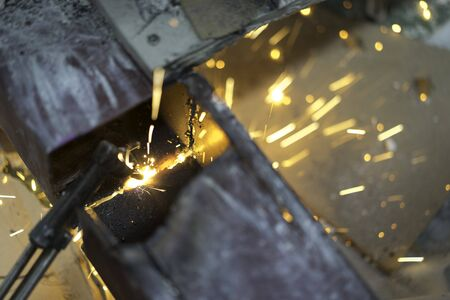 Worker making sparks from welding steel in work place.