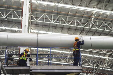 Two workers are installing piping system fabrication & installation in the factory.