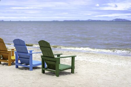 Wooden beach chairs on the tropical beach with sea and sky. Banco de Imagens