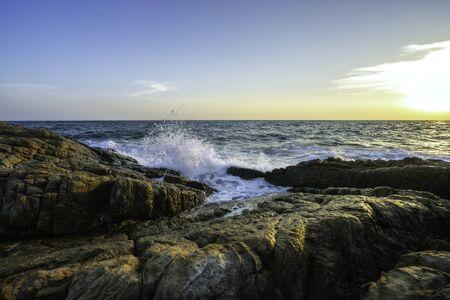 Sea waves hitting the rocks on sunset.