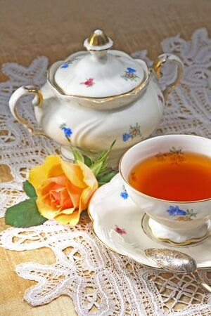 stimulate: An antique porcelain tea set an a tea rose Stock Photo