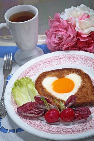 Toast with a fried egg in the form of a heart a cup of tea and flowers photo