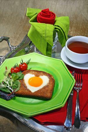 desayuno romantico: Bandeja de desayuno con huevo frito en forma de un coraz�n, una taza de t� y una servilleta doblada como una rosa
