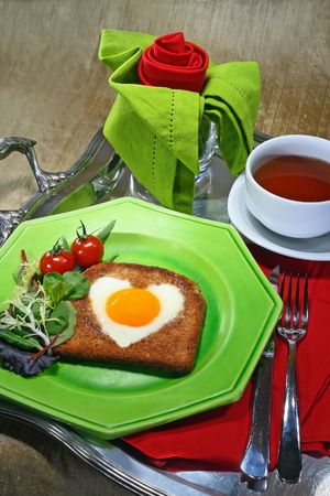 Breakfast tray with fried egg in the shape of a heart, a cup of tea and a napkin folded as a rose photo