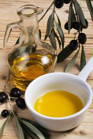 A cruet and a bowl of extra virgin olive oil and a branch with fresh olives