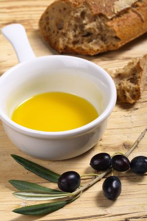 A bowl of extra virgin olive oil, a branch with fresh olives and a loaf of whole wheat bread