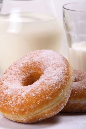 Plate of doughnuts with sugar icing and a glass of warm milk as a comfort snack photo