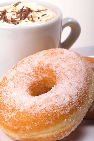 Coffee break, doughnuts with sugar icing and a cup of hot cappuchino photo