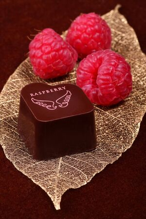 Chocolate with raspberries on a golden leaf Stock Photo - 2360866