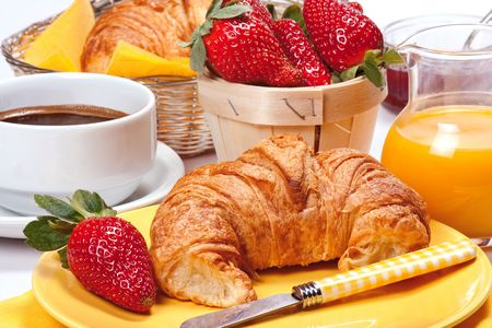 quietly: Freshly baked croissants with jam, strawberries, coffee and orange juice.   Stock Photo