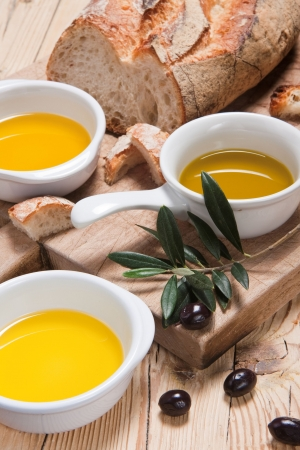 Olive oil from France, Italy and Greece with bread for tasting on a rustic wooden table