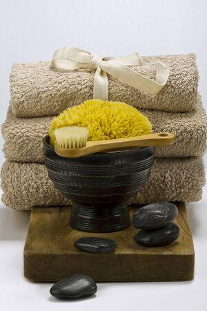 Arrangement of spa items, massage stones, towels, sponge and brush. photo