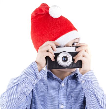film shooting: kid with christmas hat shooting with a retro style film camera. close up isolated on white background studio portrait. Stock Photo