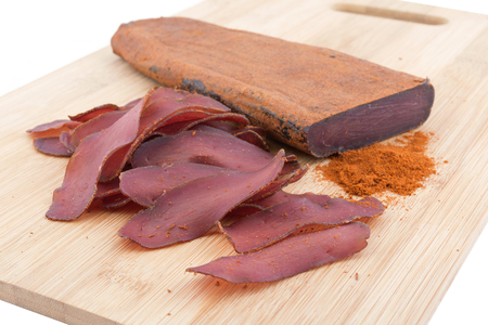 tenders: traditional Bulgarian dried meat with red pepper on wooden plank