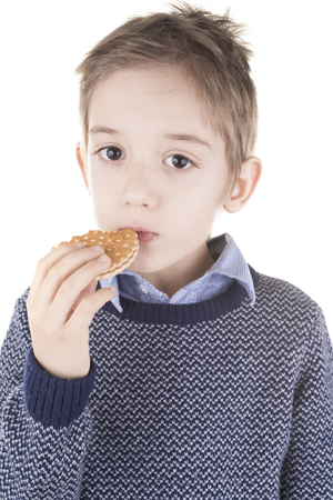 'pull over': boy eating a biscuit. studio shot on isolated white background.