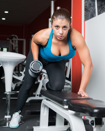 girl doing exercise with dumbbells in fitness room. Attractive fitness woman, trained female body, lifestyle portrait, caucasian model. Fitness theme.