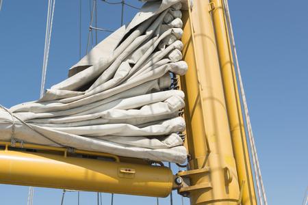 sailing boats: sailing vessel mast and folded white sail Stock Photo