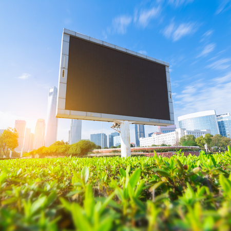 american media: Big white blank billboard in modern city over blue sky background.