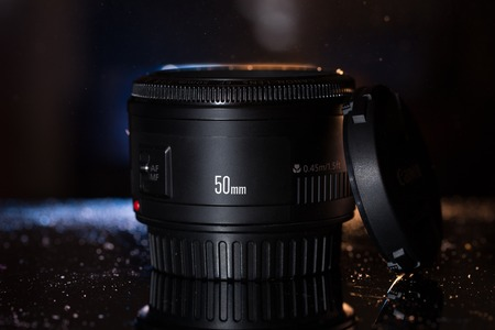 50mm: Camera lens isolated on dark background