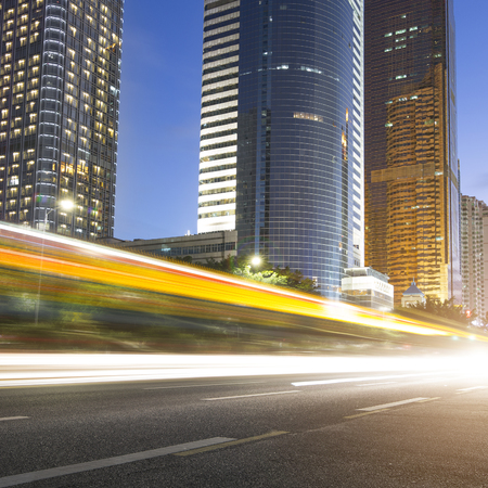 accelerated: the light trails on the modern building background in guangzhou china.