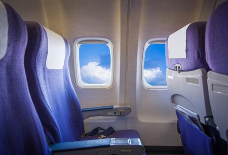 Vista del cielo y las nubes con la luz del sol desde la ventana del avión, los asientos vacíos.