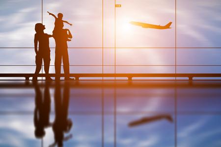 Silhueta de jovem família e avião