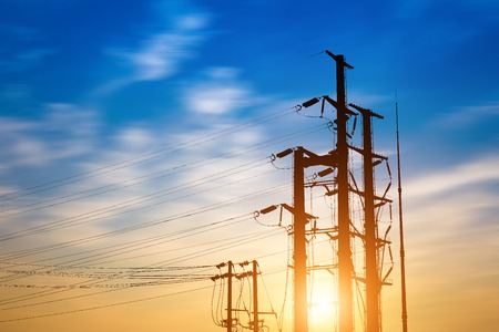 high voltage tower and electric line over cloudy blue sky on day noon light.
