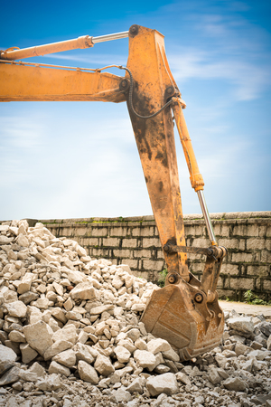 earthmover: heavy organge excavator with shovel standing on hill with rocks
