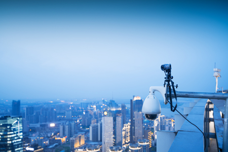 CCTV monitoring, security cameras. Backdrop with views of the city during twilight.