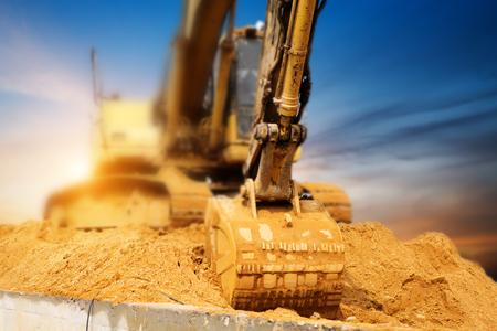 Excavadoras de máquinas en el sitio de construcción en el fondo de la puesta del sol Foto de archivo