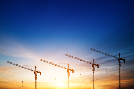 unfinished building: Industrial construction cranes and building silhouettes over sun at sunrise.