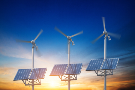 solar panels with wind turbines against mountanis landscape against blue sky with clouds Stock Photo