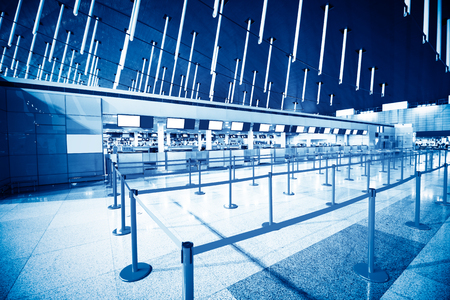The public check-in area with crowd control barriers of the city airport at early morning time.