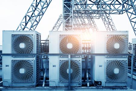 Unidades do condicionador de ar (ATAC) em um telhado da construção industrial com céu azul e nuvens no fundo. Foto de archivo - 85160661