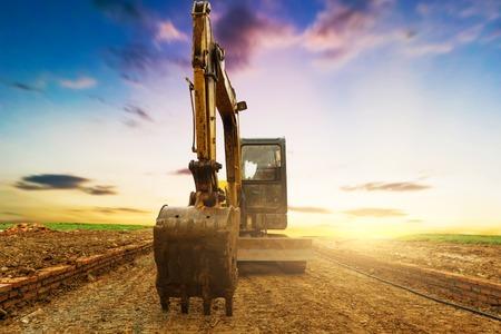 excavator in construction site on sunset sky background Stock fotó