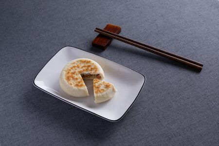 A baking cake was placed in a porcelain dish with Red Wood Chopsticks 스톡 콘텐츠