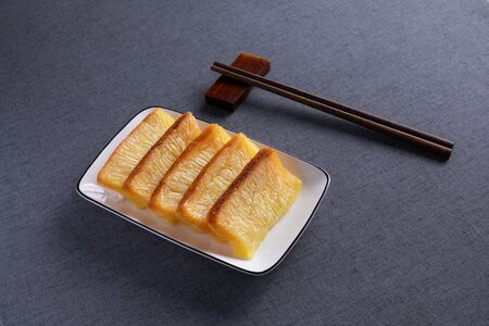 Steamed gold cake made of rice on white porcelain dishes with red wood chopsticks.