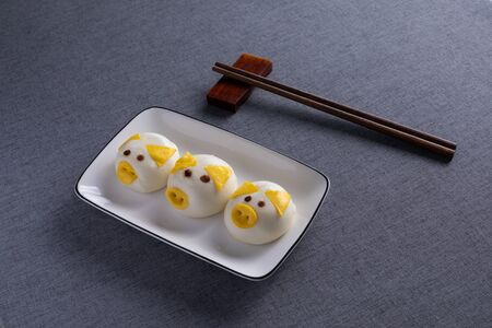 Beautiful piglet steamed bread in the porcelain plate with Red Wood Chopsticks